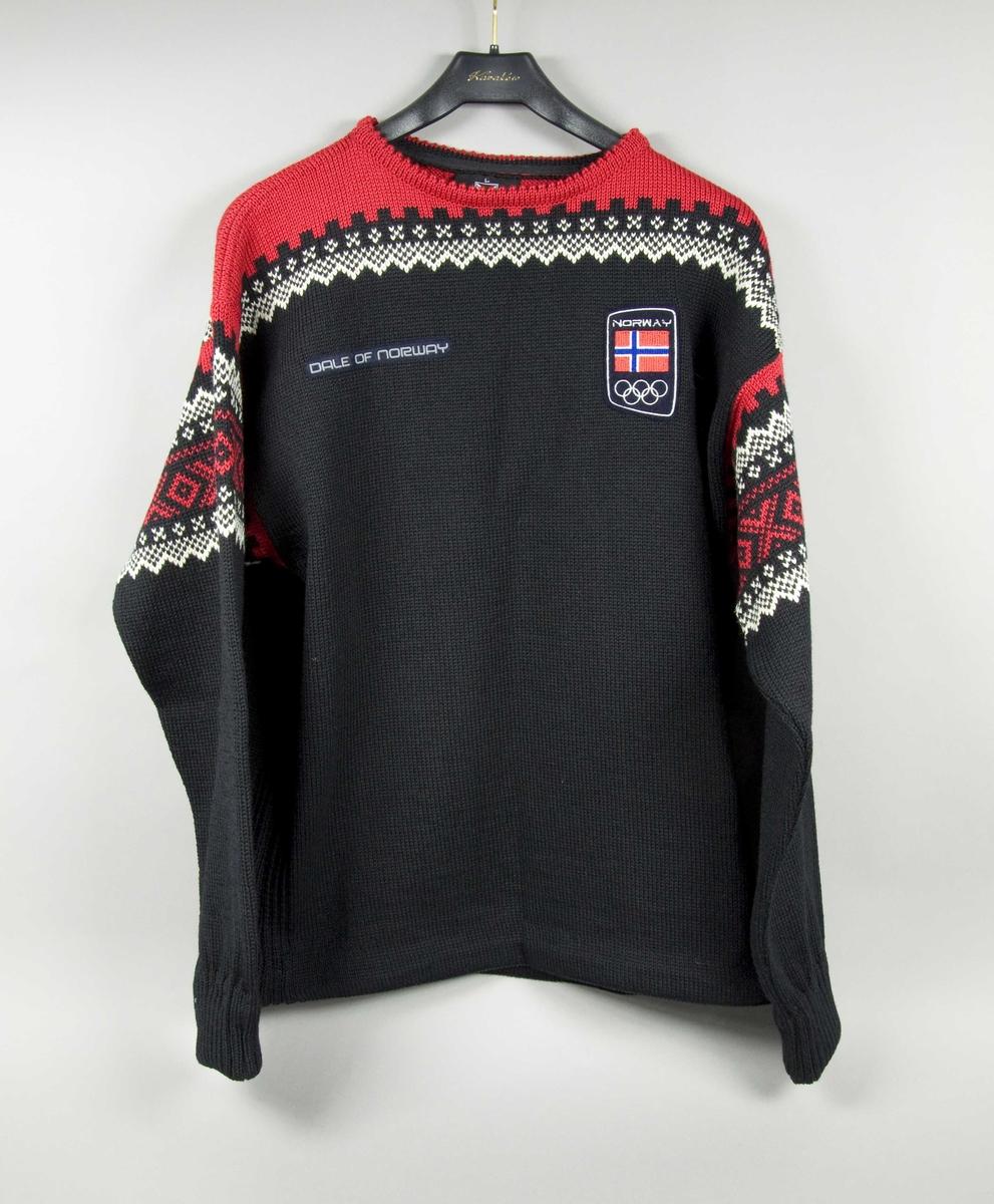 Blå, hvit og rød genser med brodert motiv av det norske flagget og de olympiske ringene på venstre bryst. Genseren har strammespenne i livet.