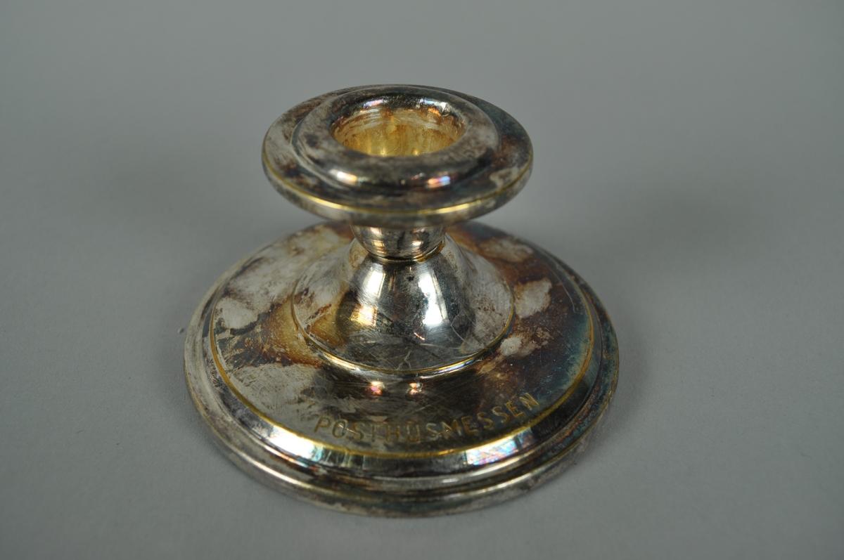 Lav lysestake for stearinlys i sølvplett med inskripsjon. Fot med filtunderlag