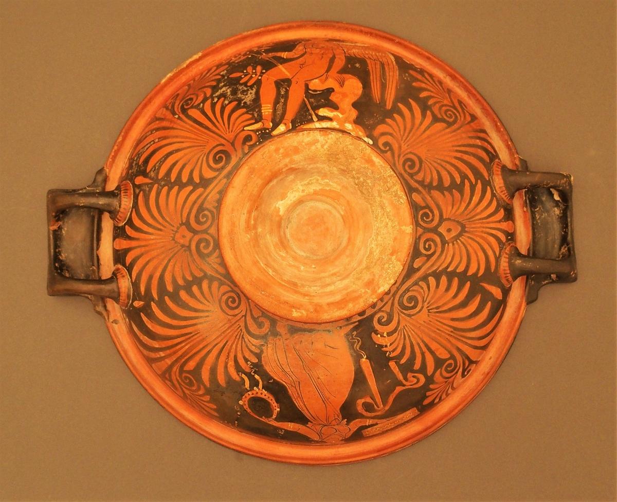 I skålens bunn naken mann (Dionysos) og kvinne med tamburin (mænade). Under dem en eggstav (kymation). Motivet er omgitt av løpende hund i sirkelform. På hankene hare og fugl. På undersiden palmettfrise (anthemion),løpende hund, mænade med tamburin og tromme og naken mann med olivengren (Apollon).