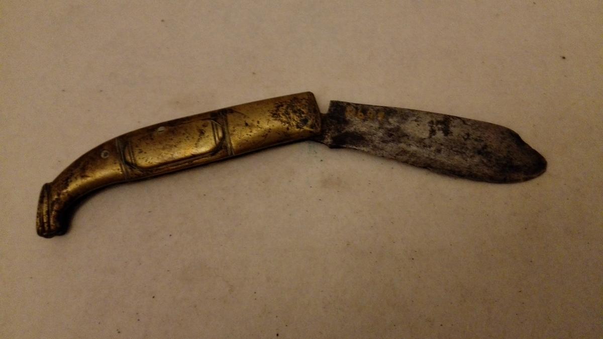 1 kniv.  Hjemmesmidd foldekniv med messing beslaaet skaft i form av en fot. Fra Lærdal.  Samtlige disse gjenstander (11643 - 53) Kjöpt ved Kjöbmand Th. Lindström, Lærdal.