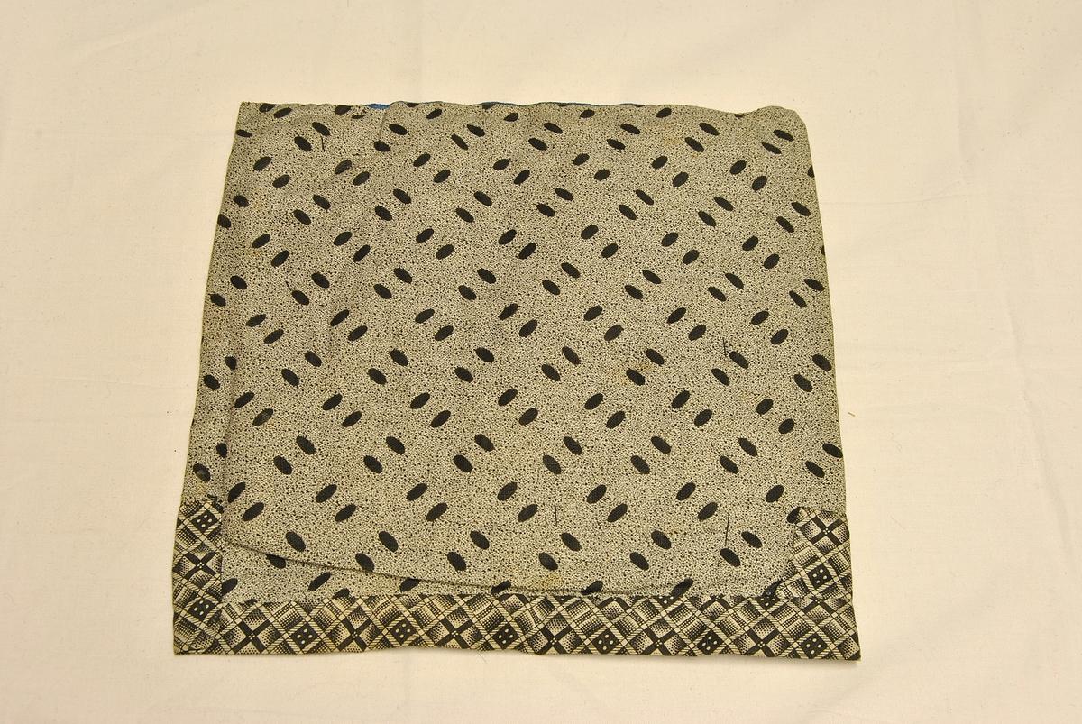 Nær kvadratisk form. Sydd sammen av flere tøystykker. Broderi i front. Pyntebånd oppe og i midten av broderiet.