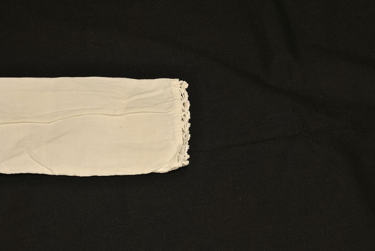 Rektangulær from. Nuppereller på kragen og ermene.
