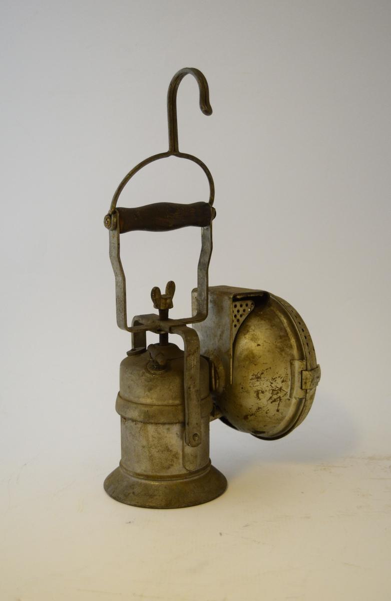Flyttbar lampe, rund beholder og rund lampedel. Håndtak med krok til oppheng øverst. Brukt i dresin (pedalstyrt fremkomstmiddel som går på jernbaneskinner) og i tuneller.