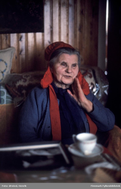 Et sjeldent portrett av Kirsten Svineng, bedre kjent som «Mamma Karasjok», sittende i sin egen stue opplyst av sparsomt vinterlys. Dette er kanskje et av de siste som ble tatt av henne i 1980, like før hun gikk bort. Mamma Karasjok ble kjent for sin oppriktige omsorg for de jugoslaviske fangene som var plassert i en tysk konsentrasjonsleir i Karasjok under krigen. Hun vandret over store områder og «mistet» mat fra sin hvite sekk langs veier og stier for at fangene skulle finne maten på vei til slavearbeidet med Blodveien som strakte seg 18 km fra Karasjok til Finland. Hennes omsorg bidro til at noen av fangene overlevde krigen. I konsentrasjonsleiren i Karasjok var det i starten ca. 450 fanger, bare 100 levde da leiren ble lagt ned bare fem måneder senere i 1942. I tillegg til disse hundre har Mamma Karasjok også hjulpet flere andre som klarte å flykte fra konsentrasjonsleiren. Hun hjalp dem som kom og søkte hennes hjelp med mat, klær og en beskrivelse av fluktruta. Dette gjorde hun på tross av at hun utsatte seg selv og familien for stor fare om tyske soldater hadde oppdaget hennes virke. Det var ikke bare Kirsten Svineng som hjalp fangene på ulikt vis, men få som ble kjent for sin innsats under krigen.  Fotograf Henrik Ørsted som har tatt bildet av Kirsten Svineng har donert ca. 1800 negativer og lysbilder til Finnmark Fylkesbibliotek i 2010.