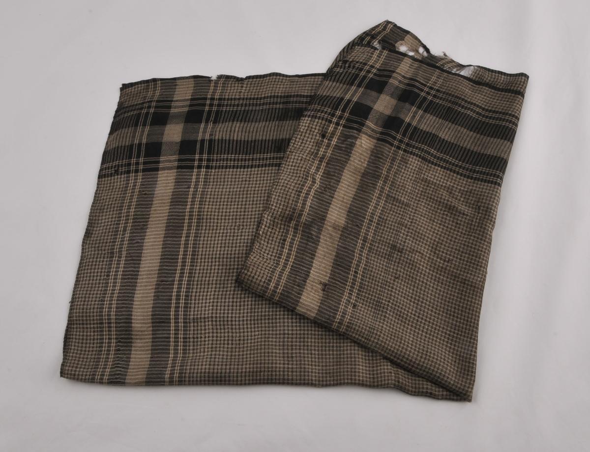 Silketørkle med smårutete grått og svart midtfelt, og med breiare svarte og grå striper langs kanten.  Jarekant langs to sider, rett avklipt og ufalda langs to sider.