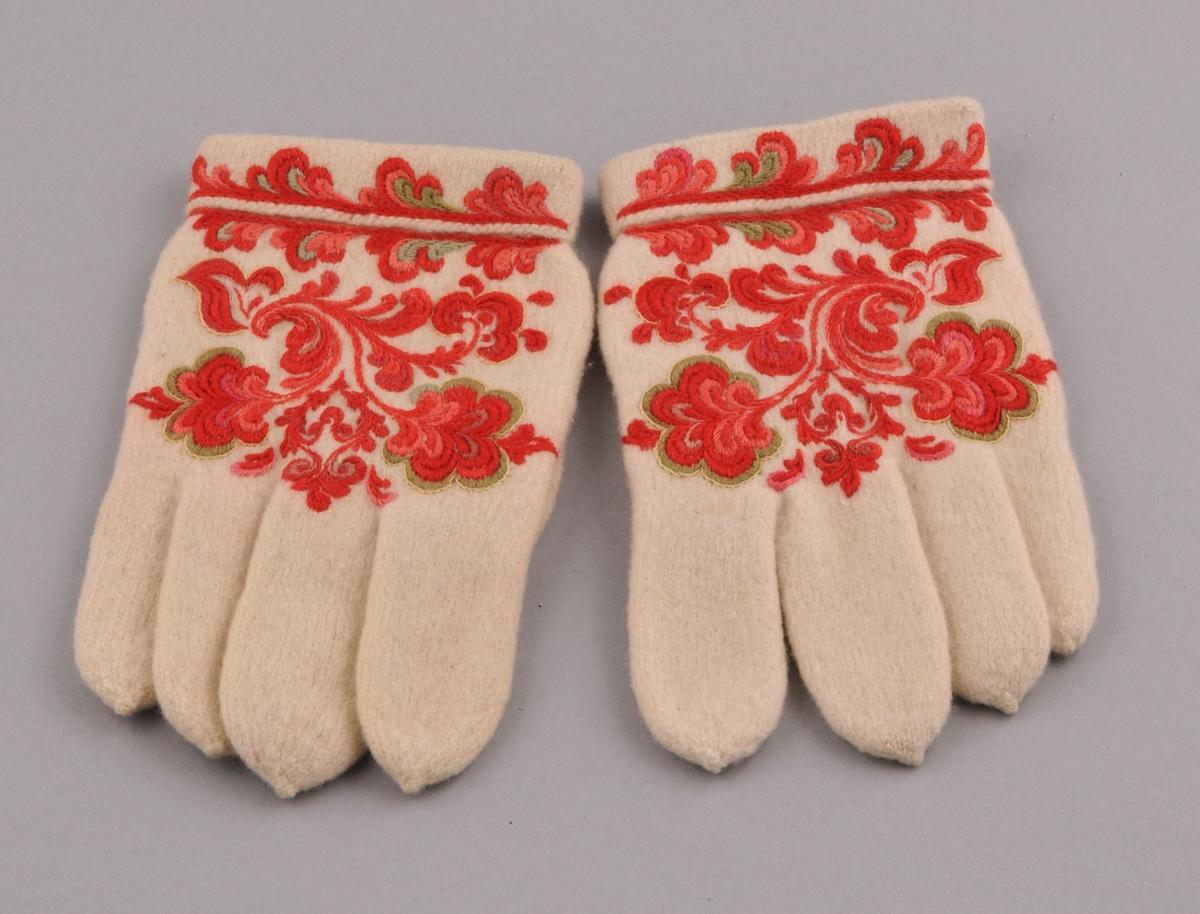 Kvite, rosesauma vottar i heimspunne ullgarn. Rosesaum på mansjetten og handbaken samt på tommelen. Nedbretta kant øverst.