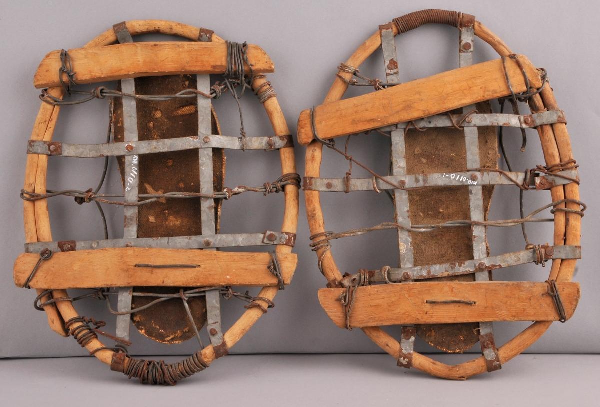 Heimelaga truger. Laga av ei vidje (grein) som er snurra til ein oval sirkel og festa saman med ståltråd. Inni sirkelen er det ei grind av flate sinkremser som er festa til vidja med metallnaglar. Under grinda er det to trestykke som er festa til vidja med ståltråd. På oversida av truga er det festa ein sole av papp/tekstil og ved sida av denne ståltrådlykkjer til feste av  reimar rundt foten.