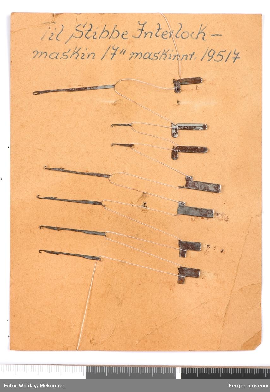 Et stivt papirark med sju nåler til strikkemaskin (Stibbe interlock).