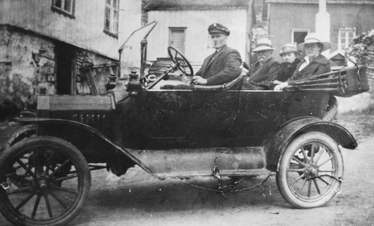 Fire personer i en T-Ford, med gårdsbygninger i bakgrunnen.
