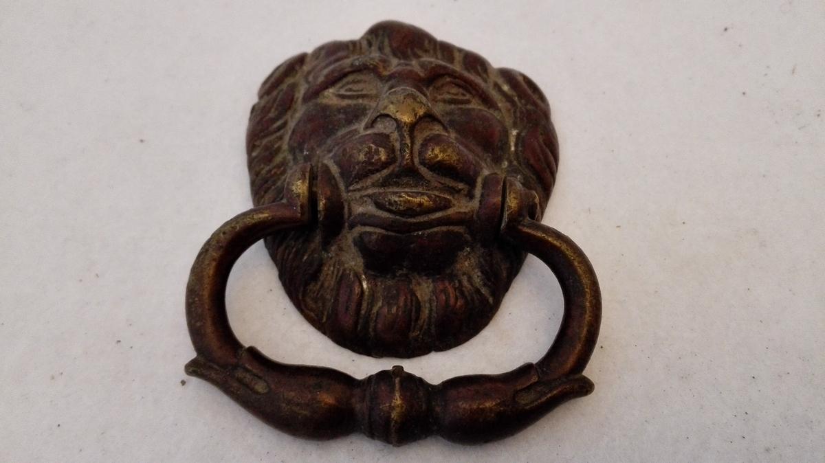 Form: Har form som løvehovuder. 1 par dragkistebeslag.  To dragkistebeslag av messing i form av lövehoder, gjennem hvis mund gaar smaa haandtag (böiler). Har været benyttet til at dra i skuffer i dragkisten.  Kjöpt av husmand Sjur Fretheim, Flaam.