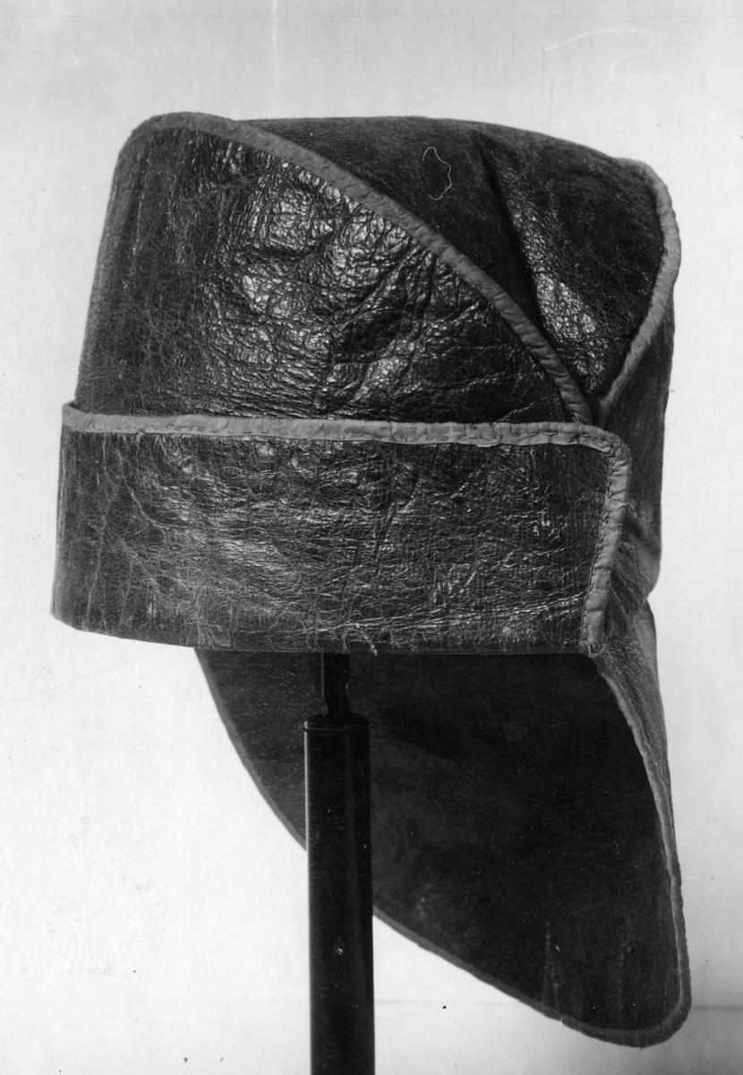 Mössa av grönfärgat läder med en stor och en mindre skärm av samma material. Fodrad med bomullstyg och kantad med sidenband. Hopfällbar.