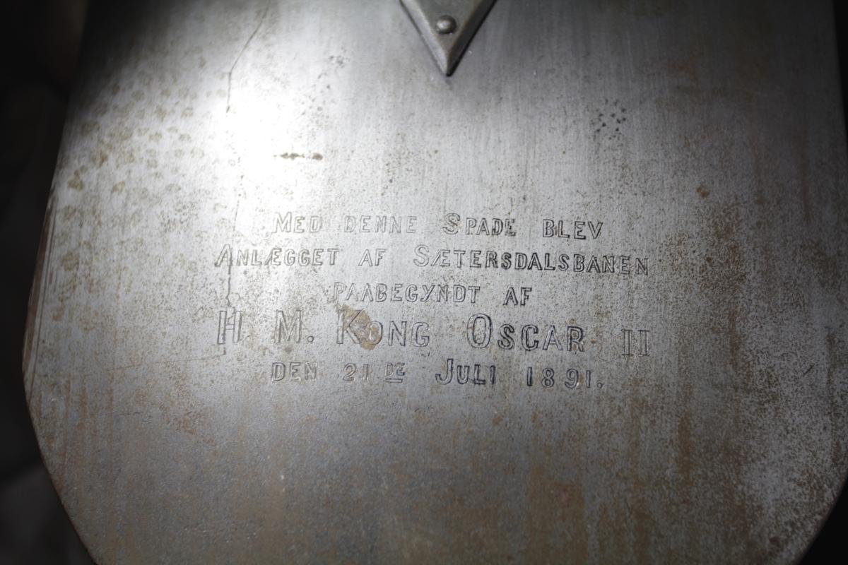 """Håndttaket i hardt treverk med oranmenter og pene utskjæringer, stjerneformede """"muttere"""" som fester selve grepet. spadebladet er festet til skjeftet med to runde plater med pigger og en arm som er skrudd fast i skjeftet. Det er gravert inn tekst på baksiden og gravert den norske riksløven fra 1844 foran, graveringen er gjort av Tobias Berglihn."""