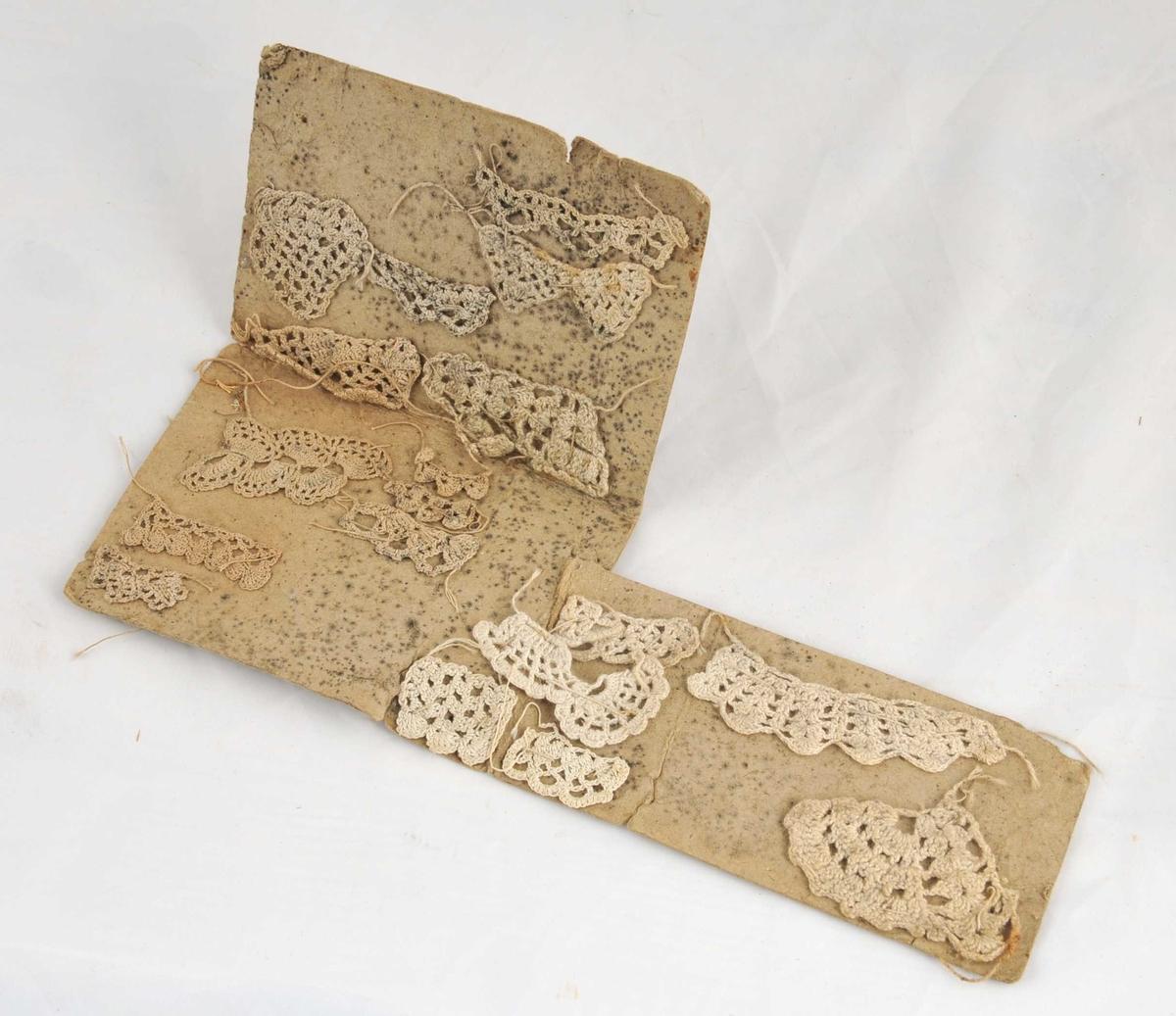 Pappbrev med prøver på forskjellige hekleteknikkar, 18 i alt. Pappen er morken. Prøvene er sydde fast med store sting. Prøvelappen er sett saman an to rektangulære stykke der det minste står vinkelrett på det største. Lappen har jordslag.