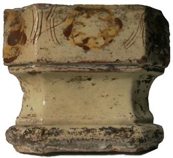 Gesimsstycke med gulvit glasyr och dekoration i brunt och gult.