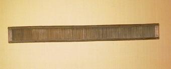Vävsked av trä där rören lindade till långsidorna med beckad tråd. 98 rör på 100 mm.