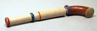 Leksakspistol som skjuter korkar av trä. Pistolen är delvis målad i brunt, blått och rött.