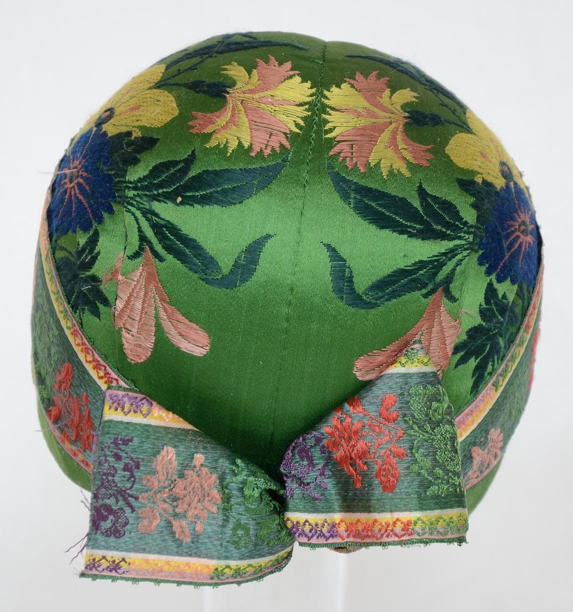 Bindmössa, klädd med mönstervävt siden, grönt med blommor. Fodrad med linnelärft.