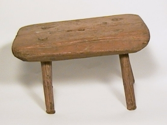 Mjölkpall med fyra tappade ben, målad i brunt.