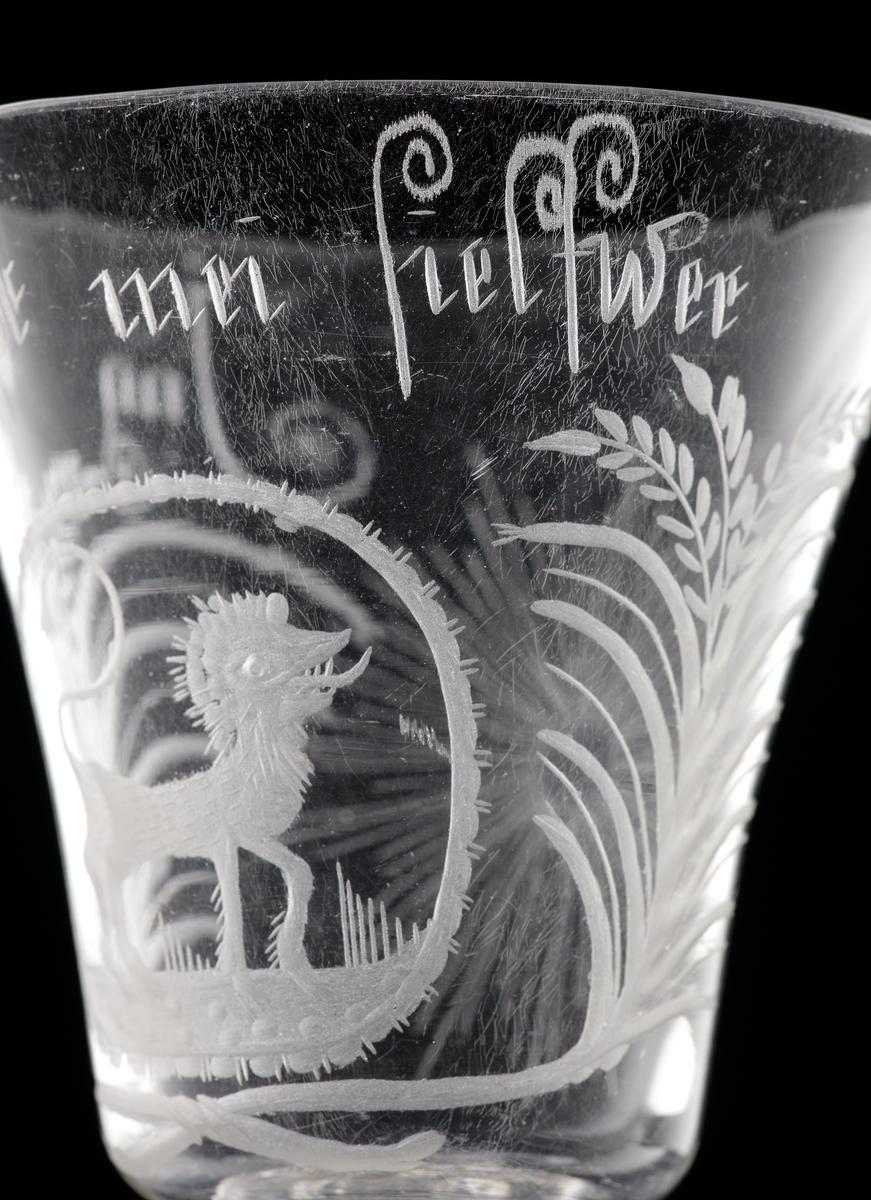 """Pokal med lock i venetiansk stil.  Graverat mönster i form av ett stående lejon m.m.. Text: """"Jag Lefwer för mei Sjelfwer"""".  Invikt kant på foten."""