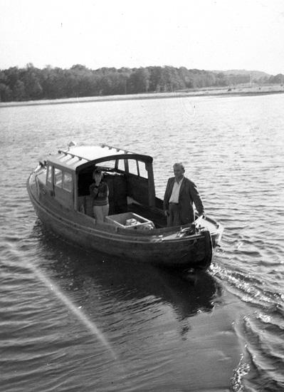 """Enligt uppgift: """"""""Månvåg"""", arbetsbåt vid Bornö Hydrografiska station. Båten är byggd 1932-1933, överbyggnaden tillbyggd av Oscar Åkermo. Ca 21-22 fot. Den äldre råoljemotorn utbytt mot Petter Diesel. I båten syns Oscar Åkermo och dottern Solveig. Fotografiet är taget år 1959""""."""