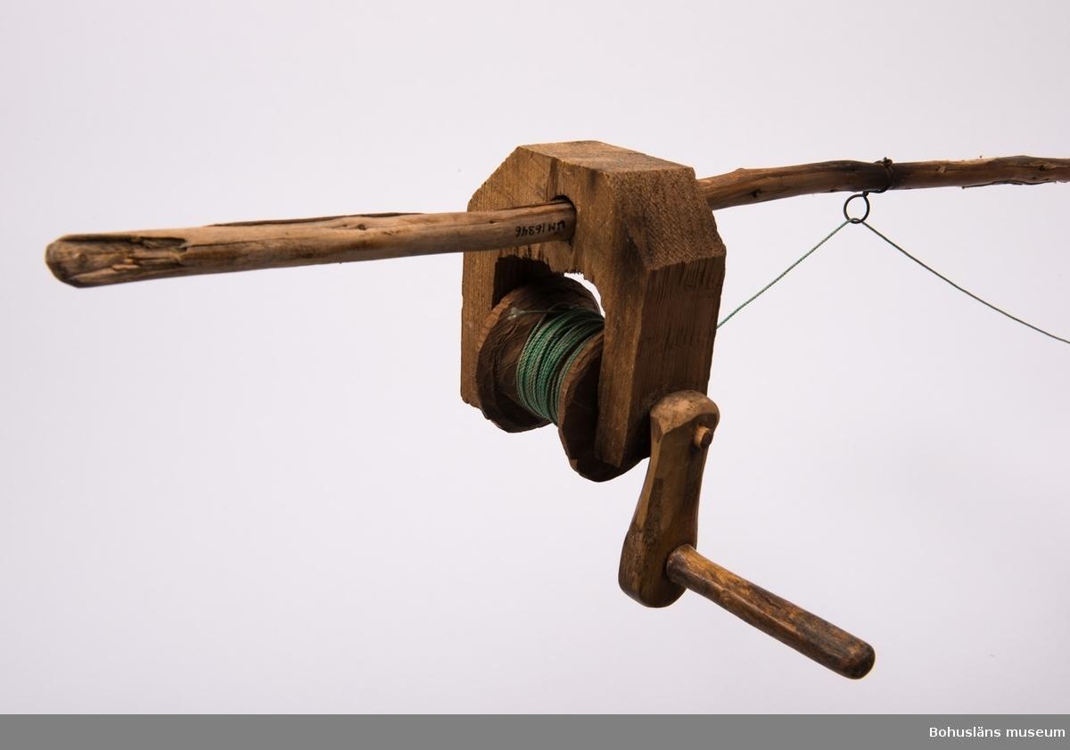 Ett hemmagjort spö med rulle. Spöt är gjort av en rak och smal naturvuxen gren. Rullen är gjord helt i trä och uppträdd på spöt genom  ett hål. Vevarm på ena sidan. Grön lina och ett hemma gjort sänke/drag  i bly och koppar.