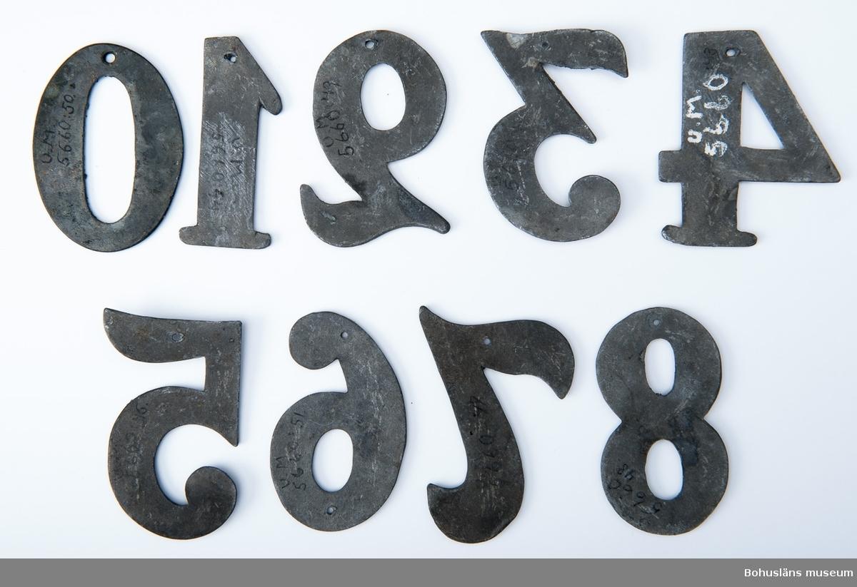 9 psalmnummersiffror av bly och mässing, höjd 7 cm.  1, 2, 2,  3, 4, 5, 6, 8, 0. UM005660:043-051.  Ur handskrivna katalogen 1957-1958: Trälåda m. siffror för psalmnummer 1-8: Bly. H.: 16 cm, m. utsirningar 9-19: Bly. H.: 9 à 10 cm; m. utsirningar. 20-28: Bly o mässing. H.: 15 cm. 29-31 Bly H.: 13 cm. 32-42: Bly o mässing. H.: 10 cm. 43-51: Bly o mässing. H.: 7 cm. 52-54: Gjutna av gulmetall. H.: 10 cm. 55-56: Vitmålad järnplåt. 57: Bly. H.: 10,5 cm.  Lappkatalog: 13
