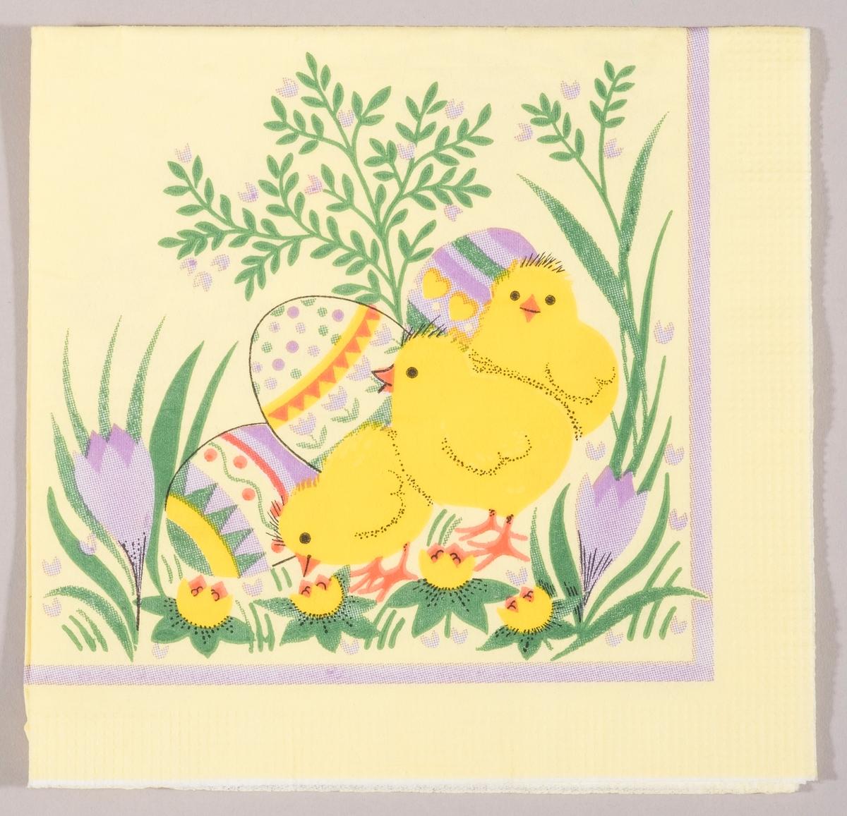 Tre kyllinger og tre store dekorerte påskeegg. Krokus og gule og lilla vårblomster.
