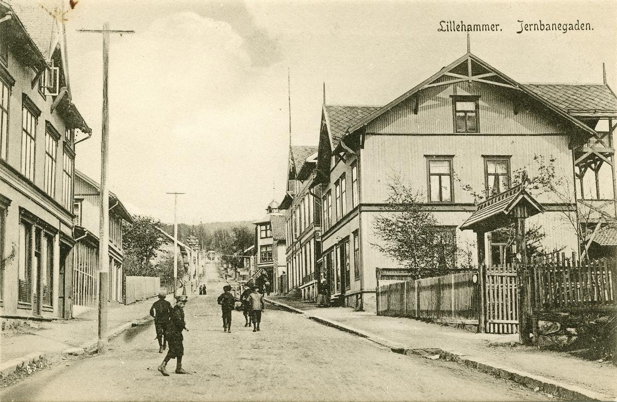 Repro: Jernbanegata, forretningshus, Rindals hus, Breiseth Hotel, Norlies kafe, inngang til Anders Sandvigs hus, mennesker, postkort