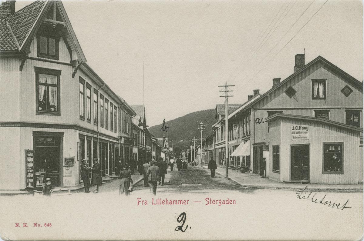 Repro: Storgata sett nordover fra Lilletorget, forretningshus, mennesker, postkort.