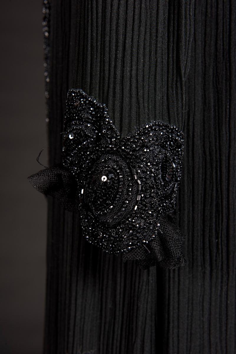 Klänning av svart goffrerat siden. Rak modell med släp och lång ärm. Dekorerad tyllkrage vid nacken. Framtill pärlbroderier med en löst hängande pärlvåd (pärlor sydda på tyll) som avslutas med pärlfransar. Baktill pärlbroderier kring halspartiet och knäppning med klädda svarta knappar från nacken till midjan. Ärmarna avslutas med applicerad pärlgarnityr och rynkad tyll samt knäpps med 10 klädda knappar.