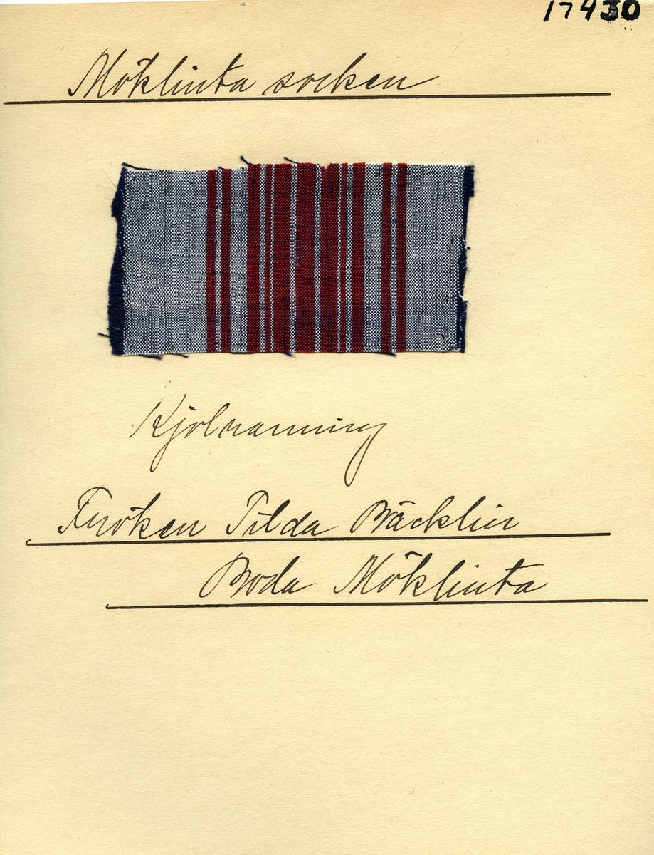 Anmärkningar: Vävprov Olga Anderzons samling. Kjolrandning, Fröken Tilda Bäcklin, Boda Möklinta. Vävprov av bomull i tuskaft, randigt. Varpen är randad i vitt och rött. Inslaget är blått. L. 980 970 Br. 520 460