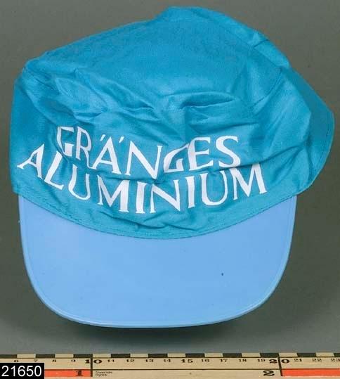 """Anmärkningar: Keps, omkring 1983.  Keps av blått bomullstyg med blå skärm av plast. Invändigt finns ett brunt svettband av plast. På framsidan finns texten """"GRÄNGES / ALUMINIUM"""". Kepsen är en gåva från Gränges aluminium i samband med länsmuseets samtidsdokumenation vid Gränges aluminium 1983. H:75 D:160"""