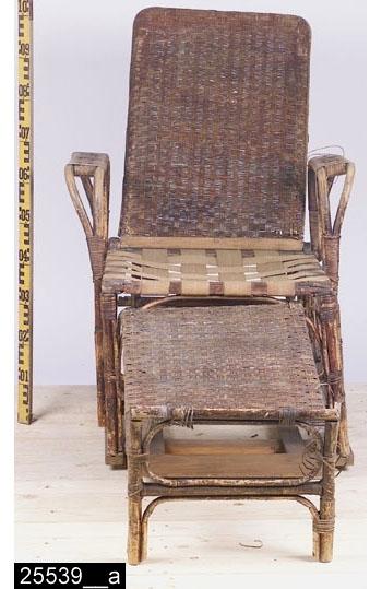 Anmärkningar: Fällstol, omkring 1900.  Ställbart ryggstöd och utfällbart benstöd. Två armstöd. Sits med sadelhjordsband (någonting saknas på sitsen). Hela stolen är fastspikad på ett senare underrede av trä. H:1140 Br:680 Dj:2050  Måtten i fälten ovan avser när stolen är fullt utfälld (vilken den inte är på bilderna 25539__a och b p.g.a. att den är för ranglig och instabil). Hela stolen är betsad eller försedd med någon annan form av ytbehandling.  Tillstånd: Stolen är mycket trasig och ranglig.