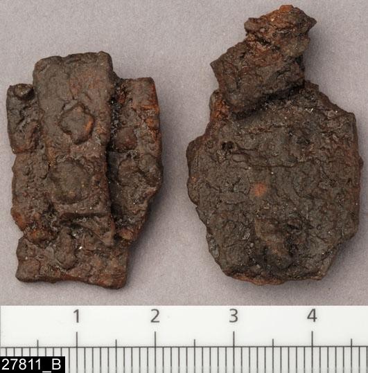 Anmärkningar: Badelunda sn, Tuna undersökt 1952-1953 Betselutrustning, från brandgrav daterad till yngre järnålder, ca 1000 e.Kr. (Vikingatid).  Hängen av järn, från grav 2. 2 st, delvis fragmentariska. Rektangulära med fiskstjärtformad nederkant. Har rektangulära fästeplattor med smala omtag lika som hängen med invnr 27422D. Hängena har tillhört en betselutrustning.  L ca 36 mm Br ca 22 mm  Litteratur: Nylén, E. & Schönbäck, B. 1994. Tuna i Badelunda. Guld kvinnor båtar I. Västerås kulturnämnds skriftserie 27. Västerås. s 94 ff Nylén, E. & Schönbäck, B. 1994. Tuna i Badelunda. Guld kvinnor båtar II. Västerås kulturnämnds skriftserie 30. Västerås. s 10 ff, 199  Fotograferad teckning A-7384,  A-7389