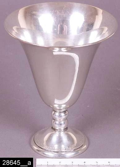 """Anmärkningar: Pokal, 1927.  Rund nedåt avsmalnande pokal. På foten finns silverstämplar, bl.a. en tillverkarstämpel """"W.A.BOLIN"""" och en årsstämpel för år 1927 """"A8"""" (bild 28645__b). Runt foten finns också en graverad text som lyder """"GÖDBOSKAPS-UTSTÄLLNINGEN STOCKHOLM 1927"""". H:110 D:90  Tillstånd: Nyskick.  Historik: Gåva från SAPA AB, Division Service, 2002. Föremålet stod i ett skyddsrum på bruksområdet i Skultuna."""