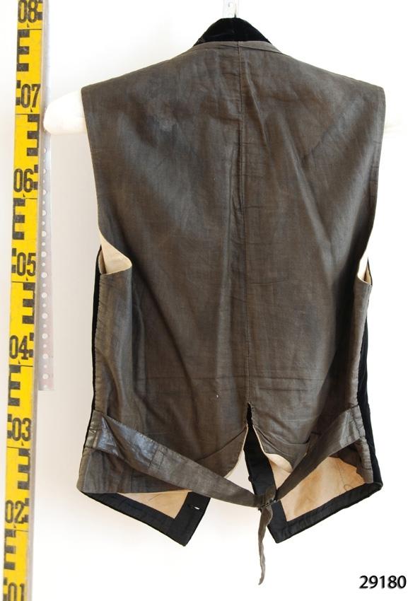 Anmärkningar: Irsta sn Geddeholm Använd av Knut C:sson Lewenhaupt född 1886 död 1951  Väst med framstycke av svart sammet med mönsterrankor kring kanterna. Grått bakstycke av bomull med band som hålls ihop med spänne i midjan på ryggen. Västen fodrad med beigt bomullstyg. Den knäpps med svarta små runda klädda knappar.