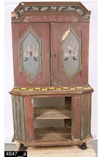 """Anmärkningar: Skänkskåp, tvådelat och rödmålat, målad datering 1844.  Överdel: Framskjutande brutet krön med bladmålad kälad bård. Målat i kranslist """"IEAS 1844 SFLD"""" flankerat av schablondekor. Pardörrar med upphöjda förkroppade spetsvinkliga speglar. Speglar med rosmåleri. Nyckelskyltar i mässing på båda dörrar. Invändigt skedhylla samt två hyllplan. H:1190 Br:1105 Dj:465.  Underdel: Framskjutande avfasad skänkskiva. Centralt placerad enkeldörr med upphöjd förkroppad och bruten spegel. Spegel med rosmåleri (bild 4847__d). Draperiformade sidoavfasningar med marmoreringar (bild 4847__b). Invändigt ett hyllplan. Står på fyra svarta svarvade fötter varav tre är av senare datum. H:945 Br:1222 Dj: 585.  Måleriet på detta skåp är intressant ur flera synvinklar. Måleriet uppvisar stora likheter med måleriet på skåpen med inv. nr. 4836 (dat. 1835) och 4549 (dat. 1848). Med största sannolikhet rör det sig om samma målare. Tre saker talar för detta. För det första är skåpen målade inom ett rimligt tidsintervall, vilket visar att en och samma målare kan ha utfört det under sin levnad. För det andra antyder proveniensen i två fall (Himmeta och Munktorp socknar) att målaren rört sig inom ett rimligt geografiskt avgränsat område. Om förhållandet varit det motsatta - att måleriet påträffats på stora avstånd hade man varit tvungen att fråga sig om det inte kan röra sig om olika målare. För det tredje överensstämmer, som påpekats, måleriet på skåpen stilistiskt. På samtliga skåp har målaren målat en blomkomposition med tre rödvita rosor och svartvita blad som sticker ut på ett sätt som ger ett flammande intryck. I krönen på skåpen är en bladbård målad i svarta och vita färger. Även bladens utformning är gemensam för de tre skåpen. Det är högst sannolikt att målaren kommer från Västmanland eftersom inga föremål av denna målarens hand eller snarlikt måleri är kända från andra landskap. Litt: Fabian Arnheim-Olofsson, Folkligt möbelmåleri i Västmanland, 2003, skåpet avbildat s31.  Tills"""