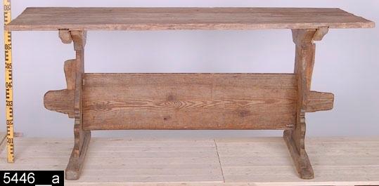 """Anmärkningar: Bockbord, 1700/1800-tal.  Löstagbar rektangulär bordsskiva. Konturerade enkelståndare på vardera kortsida (bild 5446__b). En regelbom som är profilerad i neder- och överkanterna. Regelbommen går igenom ståndarna och är på vardera sida fäst med kilar. Ståndarna står på raka sulor (bild 5446__b). H:780 Br:780 L:1760  Hela bordet går att plocka isär i delar. Sulorna och ståndarna utgör en del. Regelbommen är en del liksom kilarna och bordsskivan. Bordet kallas i liggaren för """"kalasbord"""", troligen p.g.a. att det stått i en festsal. Som regel bestod bostaden under 1700- och 1800-talen av ett eller två rum. För uppvärmningens skull bodde man endast i ett rum. Det andra rummet, i Västmanland kallat """"stugu gent emot"""" (rummet låg mittemot vardagsstugan), brukades endast som festsal.  Historik: Inköpt från hemmansägare Lars Persson, Sörberga, Munktorps sn för 5 kronor, februari 1927."""