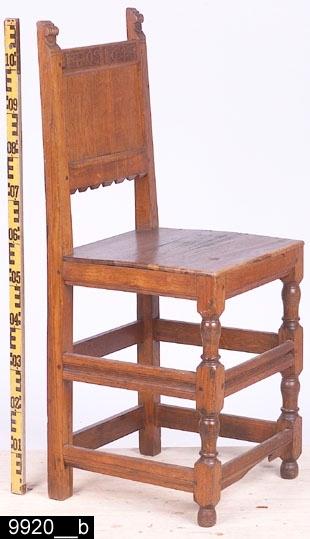 Anmärkningar: Stol, s.k. tolvslåstol (benämning efter antalet benslåar), renässans modell, 1800-tal.  Rakt överstycke med ett svårtytt dubbelmonogram, möjligen kan det utläsas som IZA och IOS (bild 9920__c). Rektangulär ryggbricka och en ryggslå med vågformad kontursågad dekor i nederkanten. Raka bakstolpar med skurna renässansornament längst upp. Sits av trä. Samtliga sargar har avfasade profilerade nederkanter. Samtliga resterande slåar är kälade och profilerade i mitten. Raka bakben och profilsvarvade framben med runda fotavslutningar (bild 9920__b). H:1115 Br:445 Dj:455  Inventarienumret är dubbelfört med invnr. 12382. Dubbelföringen går långt tillbaka i tiden, stolen är dubbelförd i liggaren. Hela stolen är av ek och har försetts med någon form av ytbehandling, troligen lack. Stolen är av renässans typ. Modellen finns/har funnits på Tidö slott. Liknande stolar finns också i Nordiska museets samlingar med proveniens från just Tidö slott (Nm 3937). Västmanlands läns museums stol är från 1800-talet och är troligen gjord efter en liknande stol eller rent av kan det vara en kopia. Möjligen är överstycket från 1600-talet, dock är det kraftigt renoverat.  Tillstånd: Nedersta främre fotslån är skadad.  Historik: Köpt från domkyrkosyssloman Hugo Bergrens sterbhus, Västerås.