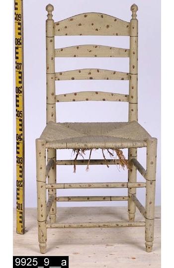 Anmärkningar: Stegstol, 1700-talets mitt eller senare hälft.  Överstycke med vågformad överkant och profilerad nederkant. Runda bakstolpar med svarvade dekorer längst upp. Genombruten rygg med tre ryggslåar som ser likadana ut som överstycket. Sits av flätad halm. Fyra runda ben med profilsvarvade fotavslutningar (bild 9925_9__b). Åtta benslåar förbinder benen. H:965 Br:485 Dj:430  Hela stolen är målad för att imitera bambu. Möblerna i serien 9925:1-12 söker imitera bambu. Sådana möbler har i omgångar varit populära i Sverige alltsedan kinasvärmeriet från mitten av 1700-talet till sekelskiftet 1800/1900. Enligt litteraturen på området tillverkades möblerna ofta för lusthus, en uppgift som också stöds av proveniensen från museets möbler - de har enligt liggaren stått i ett lusthus på herrgården Gideonsberg (riven på 1950-talet)!  Stegstolarna med invnr. 9925:7-12 (samt invnr. 28525) är inte tillverkade av Ephraim Ståhl. De är något äldre, förmodligen är de tillverkade runt 1700-talets mitt eller senast vid slutet av 1700-talet - åtminstone innan Ståhl blev mästare. Stegstolarna har målats samtidigt som, de av Ståhl tillverkade stolarna, d.v.s. omkring 1800. Stegstolarna har dock två lager av underliggande grå färg i olika nyanser av grått (även sitsen har varit gråmålad) som skymtar fram på flera ställen (bild 9925_9__c, framgår tydligast på bild 9925_10__c), vilket möblerna av Ståhl saknar. Troligen har den ursprunglige beställaren velat komplettera uppsättningen av Ståhlmöblerna och då tagit stolar som redan funnits på gården och låtit måla dem i samma stil som Ståhlmöblerna. Det råder ingen tvekan om att det bambuimiterande måleriet på stegstolarna och Ståhlmöblerna är utfört av två olika målare. För det första är måleriet mer klumpigt utfört på stegstolarna (vilket i sig pekar mot att en lokal gårds/bymålare utfört måleriet) än måleriet på Ståhlmöblerna som kännetecknas av tunnare och finare linjer. För det andra skiljer blandningen av färgen möblerna åt. Ståhlmö