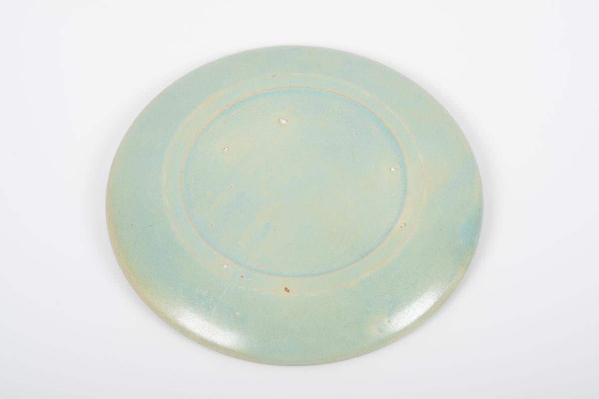 Asjett i keramikk med grønn lasur. Blanke overflater. 4 små knotter på bunnen, usikker funksjon.