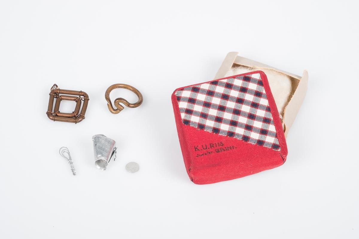 Eske bestående av bunn og lokk med bomull i. Esken er av papp. Lokket er trukket over med tekstil (bomull) i rødt og rutete mønster. I esken ligger en ring, et anheng og to miniatyrgjenstander; bøtte og visp.
