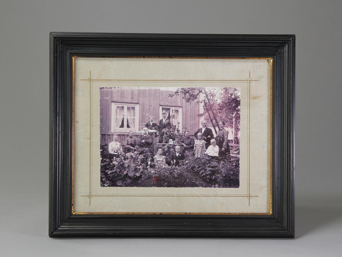 Fotografi föreställande poststationsföreståndaren Per August Nilsson och hans familj uppställda utanför poststationen i Virserum. Fotografiet uppklistrat på kartong med dekorativa streck i guldfärg. Glas och profilerad svart träram.