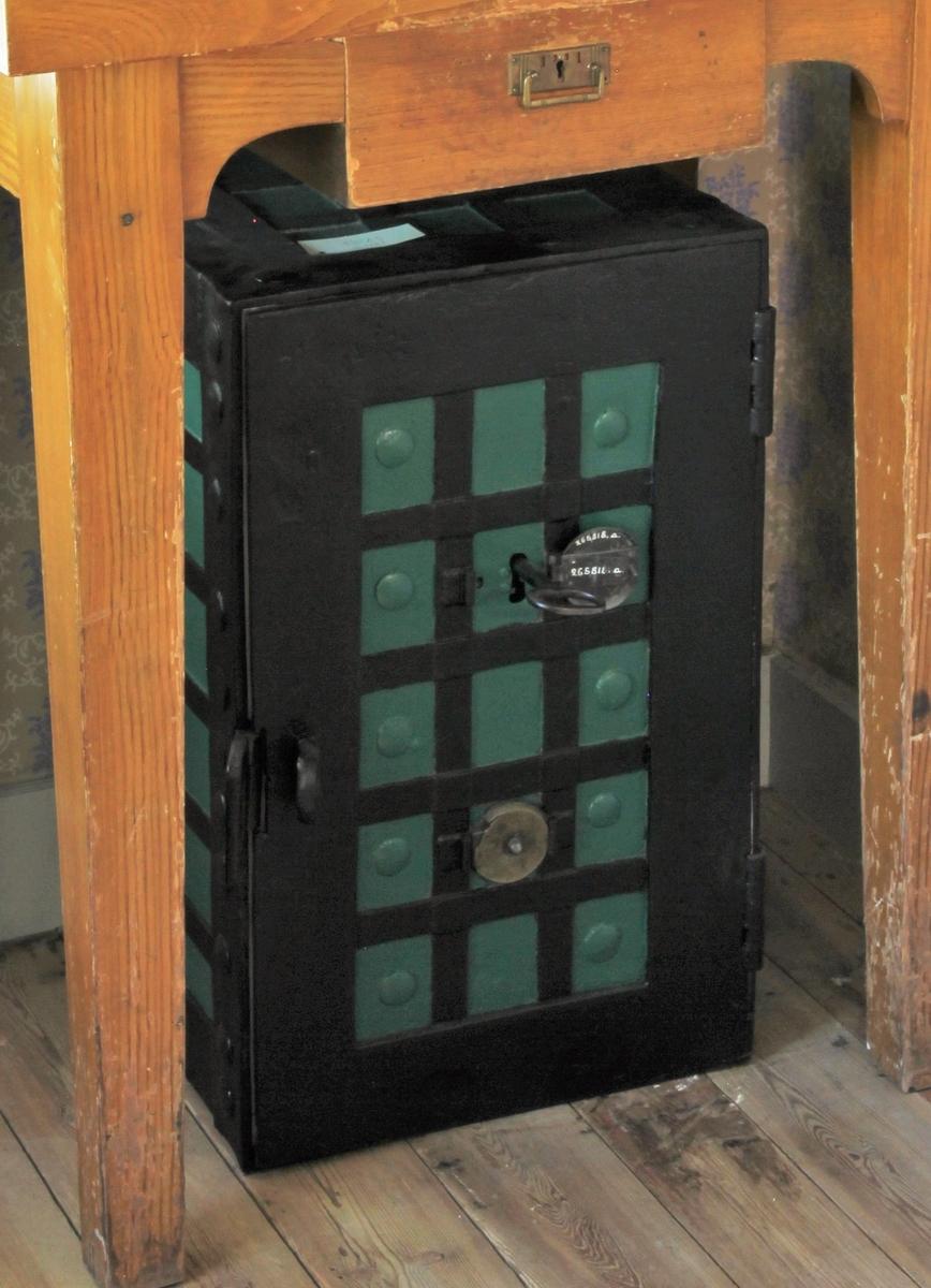 Kassaskåp av järn målat utvändigt i grönt och svart, stående rektangulärt. Dörr. Invändigt hyllplan och målat i ljusgult. Nyckel.