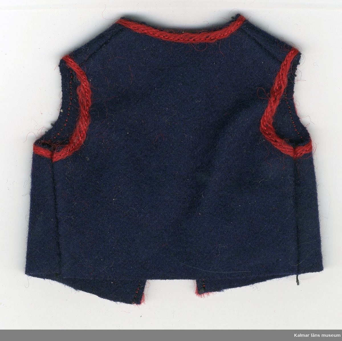 KLM 28082:83. Dockväst, herr, av textil, ylle. Del av dräkt, består av väst med röd kant runt ärmhålen, halsen, knäppningen och vid fickorna. Till nationaldräkt från: ?