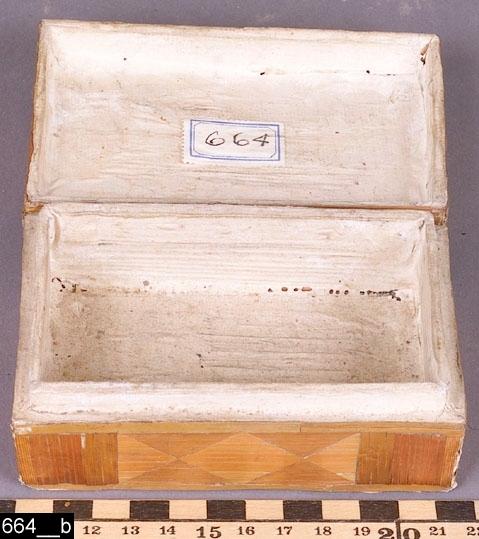 Anmärkningar: Ask, 1800-tal.  Välvt lock. Hela skrinet är av furu och är belagt med halm i olika mönster, bl.a. finns en stadsbebyggelse på locket. Invändigt är asken klädd med papper (bild 664__b). H:50 Br:120 Dj:80  Tillstånd: Skador på halmen.  Historik: Enligt liggaren från Möklinta sn, Hebo.