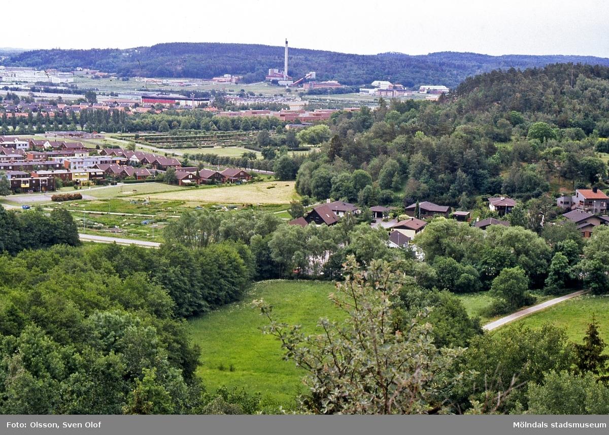 Del av Fässbergsdalen, Mölndal, i juni 1993. I förgrunden ses villorna vid Axgatan, därefter rad- och kedjehusen vid Rågkornsgatan samt Fässbergs kyrkogård. I bakgrunden ses Riskullaverket i Kärra. FD 6:8.