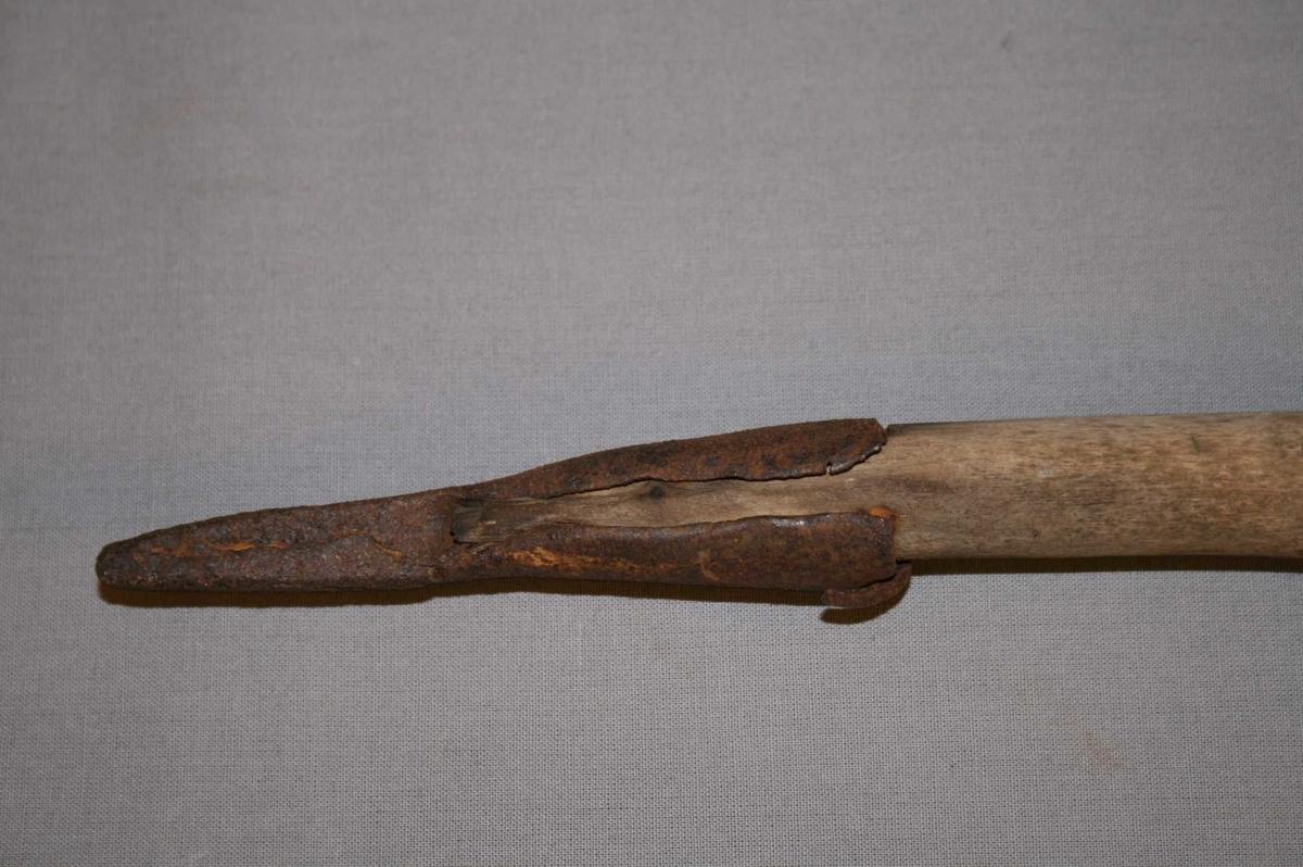 Sjølvvaksen, nokså bein stav med krok til handtak i enden. Jernholk som endar i ein spiss i andre enden.