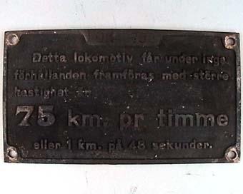 """Rektangulär skylt av svart mässing med text i relief: """"Detta lokomotiv får under inga  förhållanden framföras med större  hastighet än 75 km. pr timme eller 1 km. på 48 sekunder"""". Från ångloket SJ T 758, NOHAB Nº 708."""