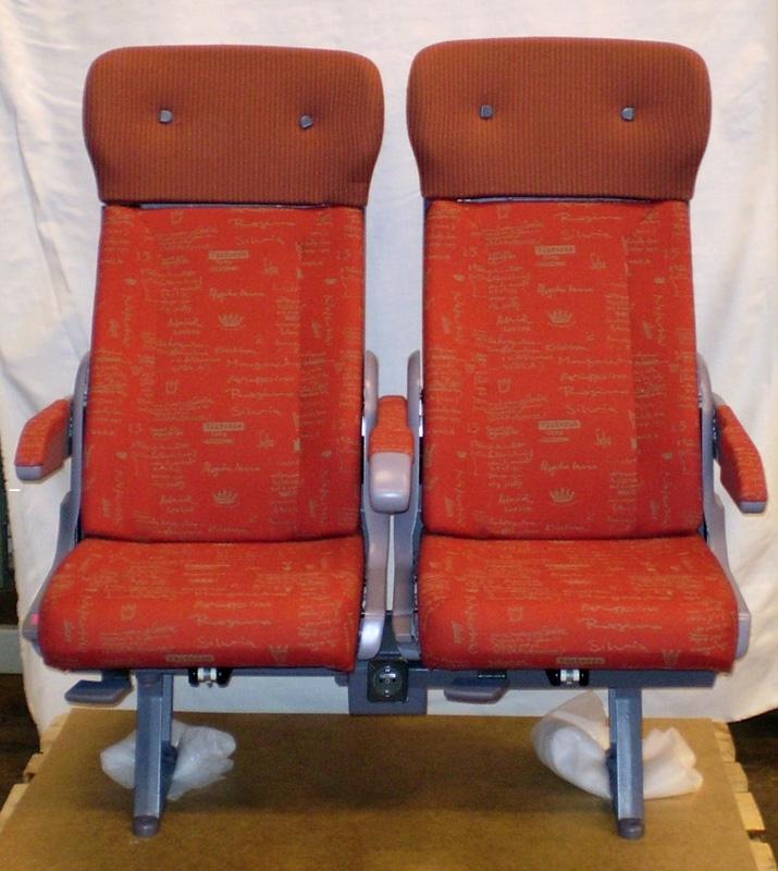 Dubbelsäte för Reginatåg. Stoppade säten med mönstrad röd klädsel, grå i övrigt. Fällbara och klädda armstöd, justerbara säten. Undertill mellan sätena ett elkontaktsuttag. På baksidan nedfällbara brickbord och nedfällbara fotstöd för de bakomsittande. Sittdjup ca: 450mm, sittbredd ca: 440mm. Sätet har tillsammans med del av väggpanel med bord Jvm19165:1-2 och dubbelsäte Jvm19164 varit utställt i visningslokal om och av Botniabanan i  Umeå (i samma hus som Umeå stadsbibliotek). Detta enligt Elisabeth Sinclair, projektledare Norrbotniabanegruppen, Pite kommun. Sinclair tror att de fick stolarna samt väggpanelen med bord från Adtranz, numera Bombardier. De frågade Adtranz om de hade säten att låna ut till visningslokalen i Umeå där de höll lunchföredrag varje fredag 11.30 - 12.00. Sätena kom sedan att flyttas till projektkontoret för Botniabanan AB på Gimonäs, till en aula för informationsmöten och var mycket populära att sitta i. Detta säte var beslutat att användas medan det andra sätet Jvm19164 var på prov.  Flertalet föremål insamlades i samband med Botniabanans invigning år 2010 och den närmaste tiden därefter. Inkluderar föremål från byggstarten och invigningen. Inkluderar även föremål från visningslokalerna i Arnäsvall (strax norr om Örnsköldsvik) och i Umeå där allmänheten kunde ta del av information om projektet med Botniabanan, samt föremål som där såldes i butik, profilprodukter och reklam- och kampanjmaterial. Även några få bruks- och arbetsrelaterade föremål från bygget med banan. Förutom insamlandet av föremål utförde Sveriges Järnvägsmuseums en dokumentation av Botniabananprojektet, man medverkade vid invigningsdagen och utförde då intervjuer, filmade och fotograferade. Material har samlats in till arkiv. Man har löpande haft kontakt med informatörer för Botniabanan AB, så som Siv Baudin stationerad i Örnsköldsvik, Strandgatan 7.  Tygprover av klädseln finns i samlingen med inventarienummer Jvm19606 Regina rand, samt 19601 med olika drottningsignaturer.